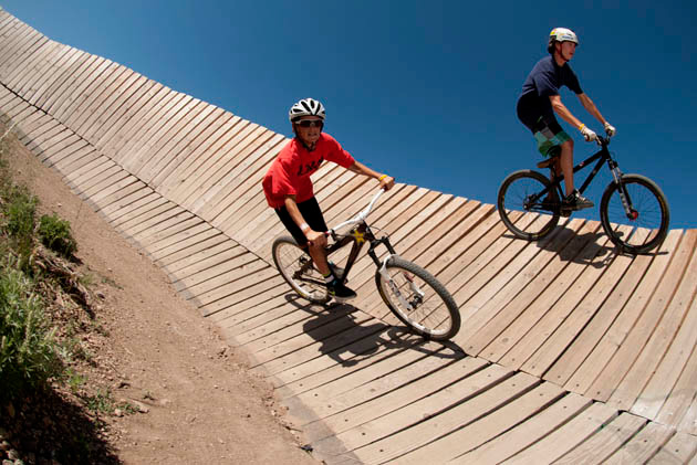 Jon Drain and Daniel Riley stick a wall ride at the Trailside Skills Park in Park City, Utah. Photo by Bob Allen