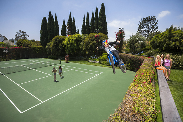 Danny MacAskill drops into the tennis court at Hugh Hefner's Playboy Mansion. Photo by Garth Milan/Red Bull Content Pool.