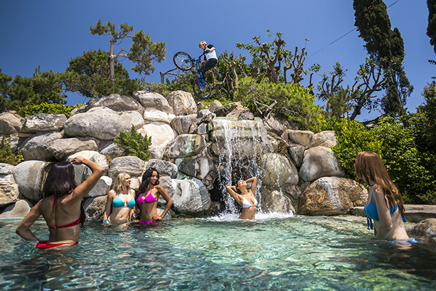 Danny MacAskill rides over the rocks atop the pool waterfall at Hugh Hefner's Playboy Mansion. Photo by Garth Milan/Red Bull Content Pool.