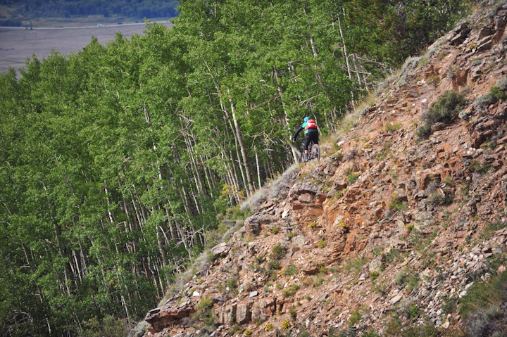 A rider carefully navigates a section of sharp rocks before diving into an aspen grove during stage 3 on the Roaring Judy trail.