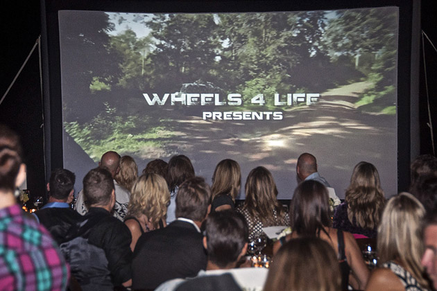 "The crowd watches a premier of Wheels 4 Life's latest film ""Riding Out of Poverty"""