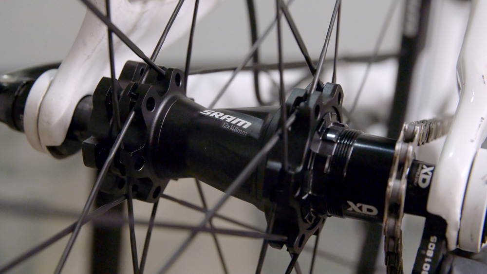 Boost 148 is a rear axle standard that widens the hub shell, effectively pushing each flange outwards by three millimeters, which both improves the spoke bracing angle and increases tire clearance.