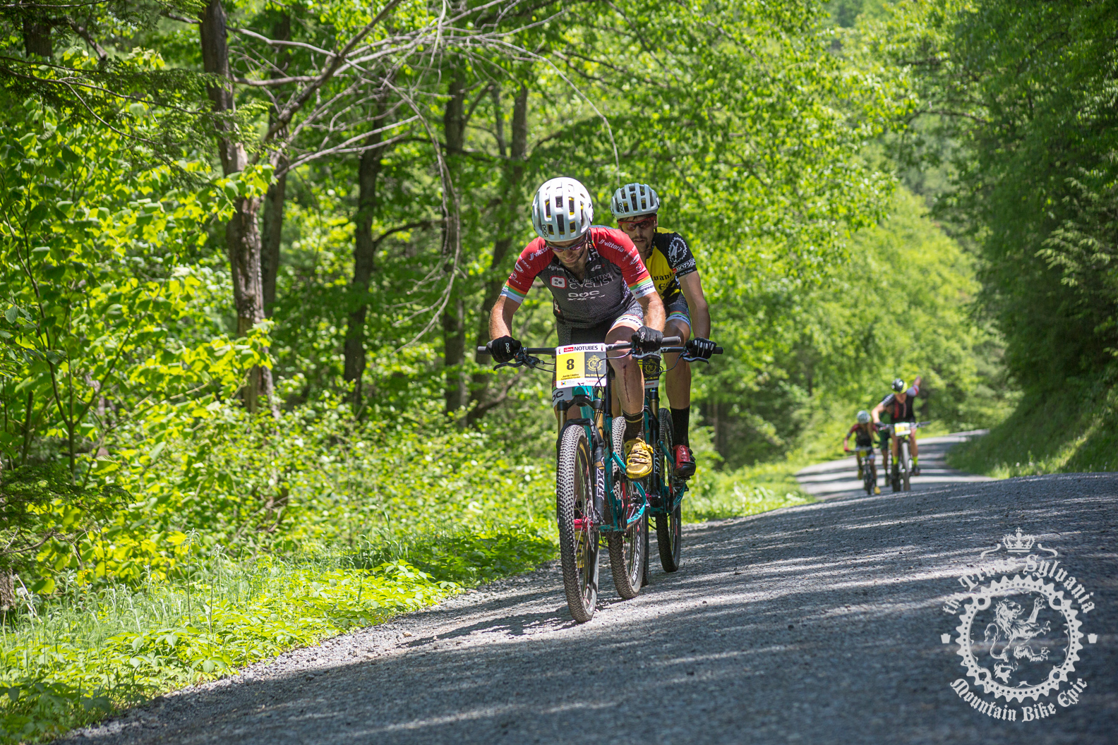 Justin Lindine (Competitive Cyclist) and Payson McElveen (Competitive Cyclist) make a break on a gravel road climb.