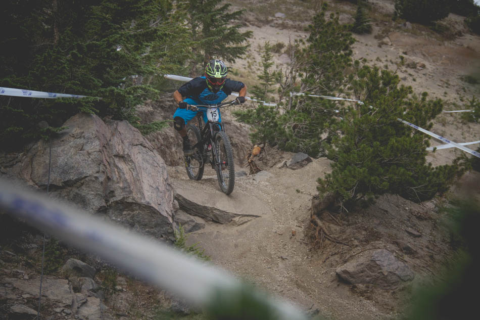 Rides left the ski run for a short jaunt in the trees. This rock was about the only solid part of a section filled with deep sand and peppered with small rock drops. More than a few riders had trouble staying upright through here, Drew Anderson, 13th overall, prepares to get loose.