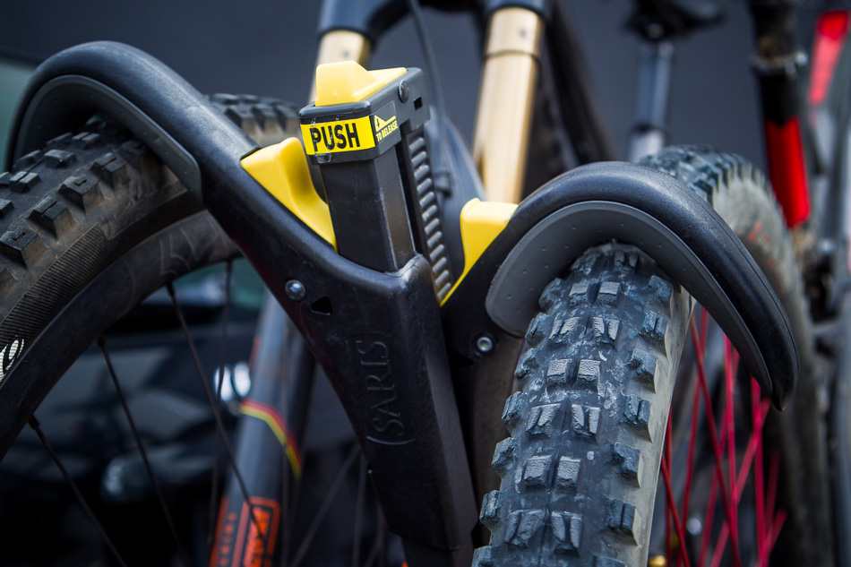 There's no need to reach down to strap wheels down, just push the top button to angle the upright support over the tire, and push the hook against it. Super quick, super solid, Superclamp.