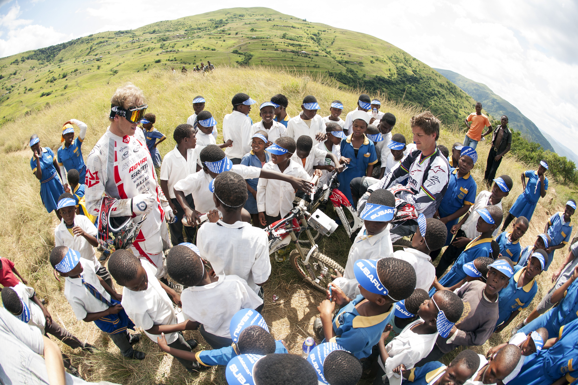 Steve Peat and Greg Minnaar surrounded by kids from the Msayana School in the Umkomaas Valley.